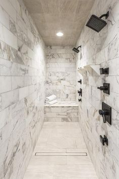 Long marble clad shower features a wood like tiled grid cieling placed over a marble shower bench alongside side-by-side oil-rubbed bronze square his and her shower heads. Farmhouse Bathroom Accessories, Modern Farmhouse Bathroom, Farmhouse Front, Shower Fittings, Shower Fixtures, Bad Inspiration, Bathroom Inspiration, Bathroom Ideas, Interior Inspiration