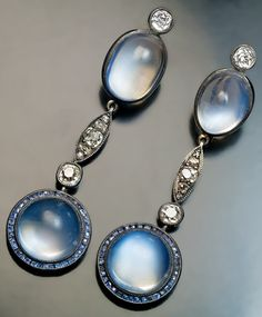 A pair of Belle Epoque Moonstone, Sapphire and Diamond Pendant Earrings, Circa 1915. Silver topped 14K gold, cabochon moonstones, calibré cut blue sapphires, old cut diamonds. #BelleÉpoque #earrings