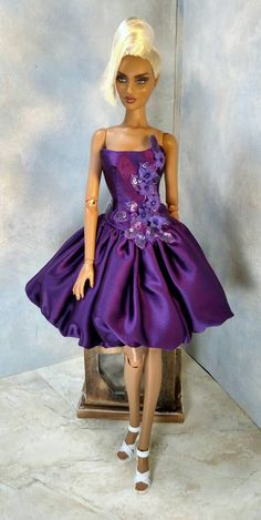 This royal purple bubble style dress is made from a deep purple silk Charmeuse and purple silk dupioni. Embellished with purple sequins, flower petals and crystals. Corset closure for a snug fit. Lined in purple silk and green tulle. From a smoke and pet free home