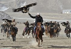Akqi county, the Xinjiang Uighur autonomous region of China: Kyrgyz herdsmen hold falcons during a performance to celebrate Nowruz