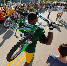Green Bay Packers defensive end Mike Daniels (76) carries a young boys bike after it was to small for him to ride before NFL football training camp Saturday, July. 28, 2012, in Green Bay, Wis.  by Mike Roemer