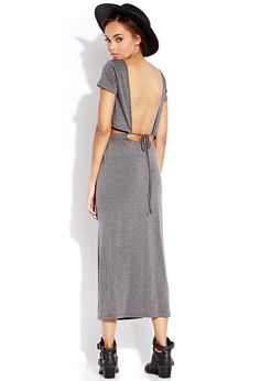 A split maxi dress featuring a waist cutout and open back. Round neckline. Short sleeves. Elastic...