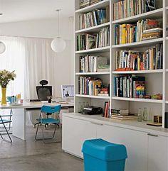 No andar superior deste apartamento dúplex, fica o estúdio do casal de designers. Para adequar o ambiente à função, optou-se por um acabamento neutro para a ampla estante de madeira laqueada. Assim, as cores vêm dos livros, das revistas e dos objetos. Projeto de Domingos Garcia.