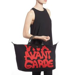 Graffiti-inspired lettering by fashion designer Jeremy Scott splashes a roomy tote that folds into a conveniently compact shape for travel and storage.