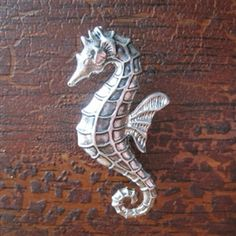 Seahorse drawer knobs / cabinet pulls in Silver metal  Seahorses are one of the few creatures where the male is responsible for carrying the eggs in a pouch on his tummy until they hatch! They are also not great swimmers; males rarely stray more than a meter away from their home. These drawer knobs featuring one of the cutest sea creatures would look great on a dresser or cabinet in a sea-themed room or at a beach house!