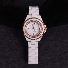 Дамски часовник с бяла пластмасова верижка и ефектен циферблат. Малки блестящи камъчета са поставени в самият циферблат и около него а металните части са  красиви и златисти