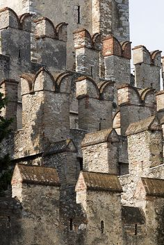 Crenellations Noun Architectural features at the top of a wall of a castle A specific type of castle defense featuring multiple rectangular spaces through which arrows may be shot Castle walls and crenellations at Sirmione, Italy by RoCam Beautiful Buildings, Beautiful Places, Lake Garda Italy, Templer, Castle Wall, Seen, Innsbruck, Fortification, Medieval Castle