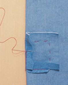 Turn the shirt inside out. Fold back the 1/2-inch of excess fabric so it's flush with the folded edge of the hole, folding the corners over each other. Insert the needle through the folded edge of the patch; stitch up diagonally through the folded edge of the shirt, joining the two fabrics. Continue all around the square. Remove the basting thread.