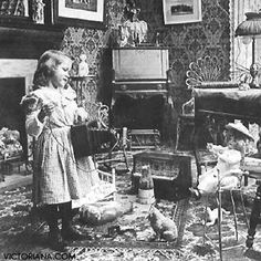 Girl plays with toys, including antique doll in highchair.