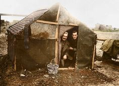 THE SOMME in Color 1916-2016: Two British soldiers look out from a ramshackle hut that served as their home on the frontline during the Battle of the Somme in 1916.