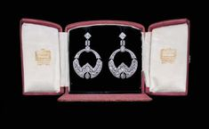 PAIR OF DIAMOND EAR-PENDANTS, BY CARTIER  Each designed as an old mine-cut diamond articulated hoop of stylised cartouche motif with a pear-shaped diamond drop to the diamond surmount and top, circa 1929, in its original Cartier pink leather fitted case Signed by Cartier, London