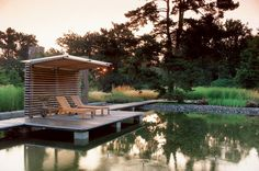 Private garden by Nordfjell Landscape Architecture. Amazing covered deck by a pond.