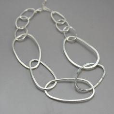 Moderna, única y atrevida, este collar de plata esterlina es hechos a mano de alambre de plata Argentium de alto calibre. Grandes vínculos de la plata, en forma orgánicas formas ovaladas y luego martilló los plano para capturar la cantidad justa de luz. Hay 5 grandes en el frente de la cadena y luego fui a un enlace más pequeños alrededor del cuello para impedir que los bancos alrededor de la pieza. La longitud es ajustable desde enlaces de 16-18 y por el más grande, esto encaja más como una…