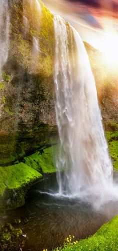 Seljalandsfoss waterfall in Iceland!  This waterfall in unique because you can actually walk behind it!  Click through to see more amazing waterfalls in Iceland!