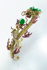 """Inheritance brooch by Wallace Chan featuring a Chinese totem called """"the dragon educating his son"""" commonly found in Qing artefacts. The ball is imperiale jadeite of a particularly intense emerald green colour and appears to float mysteriously with no metal claws on view as the father hands his legacy to his son."""