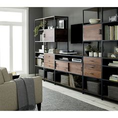 Shop Knox Media Console with 2 Tall Storage Bookcases. This custom media storage solution flanks an open and airy console with matching tall storage bookcases, each with a trio of stacked drawers and a cabinet with a reversible door.