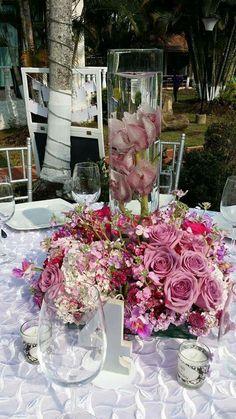 Centro se mesa con cilindro y flores rojas y vela flotante
