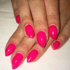 Neon coral pink stiletto gel nails with gel polish.