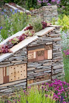 Siermuren met insectenhotels en ruimte voor vetplanten.