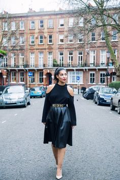 Alya Mooro rocking all black in London's streets. Cut out sweater Reformation, vintage Moschino belt, wet look boohoo over the knee skirt, nude Kurt Geiger heels and slicked back hair.