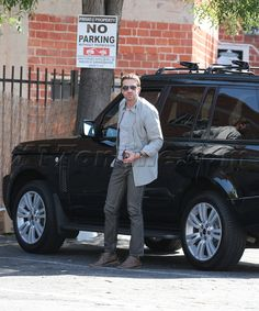 Gerard Butler stepping out of his black Range Rover