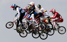 Riders take a jump in the men's BMX quarter-final run at the BMX Track in the Olympic Park, on August 9, 2012.