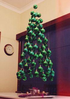Des boules de Noël suspendues au plafond pour fabriquer un sapin de Noël original