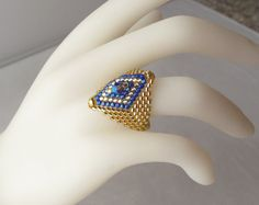 Woven Ring with Blue Crystal and Diamond Pattern on Gold Band