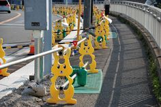 A set of yellow rabbit-shaped barrier supports to guide pedestrians around a roadworks site...