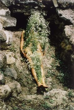 klept0cracy:  Ana Mendieta was a Cuban born artist (1948-1985) who used her body to deal with issues of spirituality and cultural heritage. This photograph, called Flowers on Body (1973), was the first of her Silueta series of photographs depicting earth/body sculptures