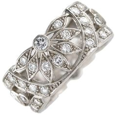 Platinum and Diamond Wedding Band  1930's - Wide and intricately designed platinum band.Set with round and baguette cut diamonds.Unique open work with opposing half flowers front and back. Sides set with angled baguettes.