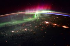 Bright lights of an aurora and city lights on Earth photographed from low Earth orbit