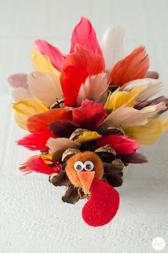 Make these adorable pinecone turkeys as the perfect Thanksgiving decoration using faux feathers and some glue. Great for kids and adults alike! - thanksgiving quo - How To Make Pinecone Turkeys With Feathers