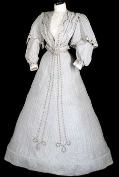 """Fawn twill walking dress, circa 1895. Full, caped sleeves. Bodice has cream figured insert and cuffs. The skirt is embellished with applied woven braid. Label: """"Au Progrès, Aix-en-Provence,"""" via Christie's"""