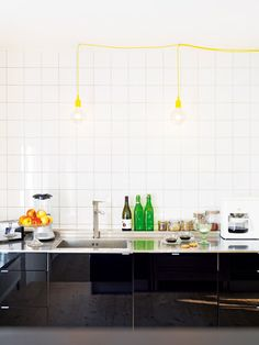 love the shiny black cabinets, white tile and a pop of yellow lighting