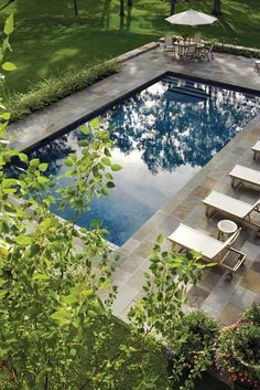 Rectangular pool with ample bluestone deck, larger on one side for chaise lounges