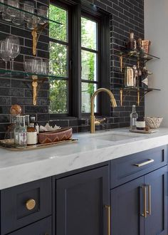 Chic wet bar features dark blue shaker cabinets adorned with brushed brass hardware paired with white marble countertops and a glossy black tile backsplash.