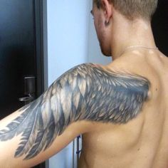 Man With Tattoo Wings On Back Of Arm And Shoulder