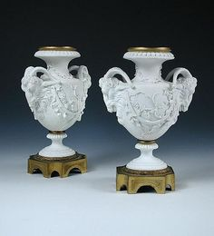 A pair of 19th century 'Sevres' bisque vases, the baluster shapes with ram's head handles applied with grapevines and ormolu mounts, interlacing L and central F marks, 19.5cm high (W) (2)