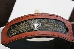 Terracotta dog collar with unique greenish handprinted underlayer and antic silver, patina ornamentation. Hand sewn and durable: composed of 3 layers, each 4mm thick, with strengthened areas of the largest pressure (buckle, D-ring). Very comfortable to wear: Firmness of the collar doesn't lessen the dog pleasure of wearing it!  Not only does the collar look great, it is robust and gains with the usage.  This collar like all SAURI collars from A collection is a UNIQUE product. It means that…