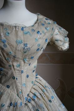 1852 Bodice - Full ball gown in taffeta covered with ivory veil of ivory silk embroidered with blue flowers and blue. _____ The panty is closed on the back by a series of hooks.