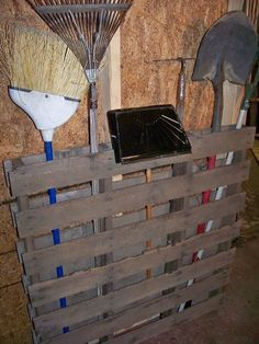 An old wooden pallet nailed to the wall of garage or storage building to hold gardening tools .