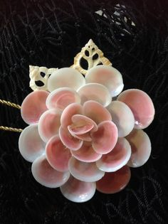 "Seashells handmade into this gorgeous shell flower. All Naturally colorfull shells. A Beautiful Ornament to treasure. This ornament comes in 2 Sizes - small Is between 2""-3"" inches large is between 3"""
