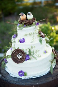 wedding cake decorated with bird nests, birds, and greenery with purple flowers
