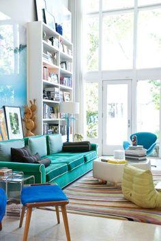 decoração com sofá colorido, sofá verde estante alta com livros