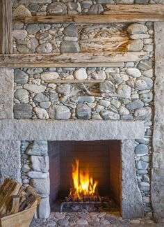 Rustic Family Room by Hutker Architects would have been easy to just make this fireplace surround of field stone but the insertion of raw timbers and driftwood make it almost an art piece . Stacked Stone Fireplaces, Rock Fireplaces, Rustic Fireplaces, Outdoor Fireplaces, Beach Cottage Style, Beach Cottage Decor, Stove Fireplace, Fireplace Design, Fireplace Ideas