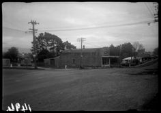 Butchery on the corner of Valley Rd (Glendale Rd) and West Coast Road, Glen Eden, 1949. The Robertson family had the butcher's shop from 1920 until 1961. Methodist Church in the background. JTD-12A-01494. Read more in the book 'In those days, an oral history of Glen Eden' edited by Pauline Vela, p.60-61.