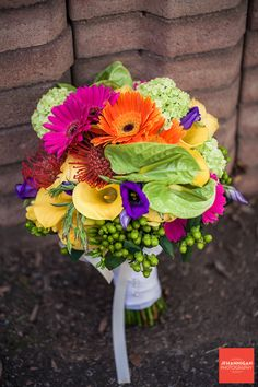 colorful bouquet against bricks.  Photo by JF Hannigan Photography