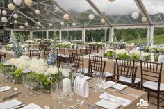 A beautiful Clear span tent with lanterns and Family Style tables with faux burlap linen.