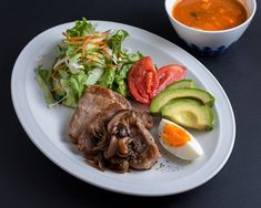 Pork chops sautéed mushrooms and onions, paired with a salad, slice of avocado, egg, and tomatoes makes a perfect healthy dinner